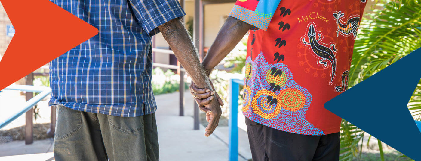 A close-up of a NWRH staff member holding the hand of an aged man as they go for a walk.